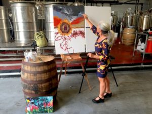 Artist Caroline Karp live painting at an event in Tampa.