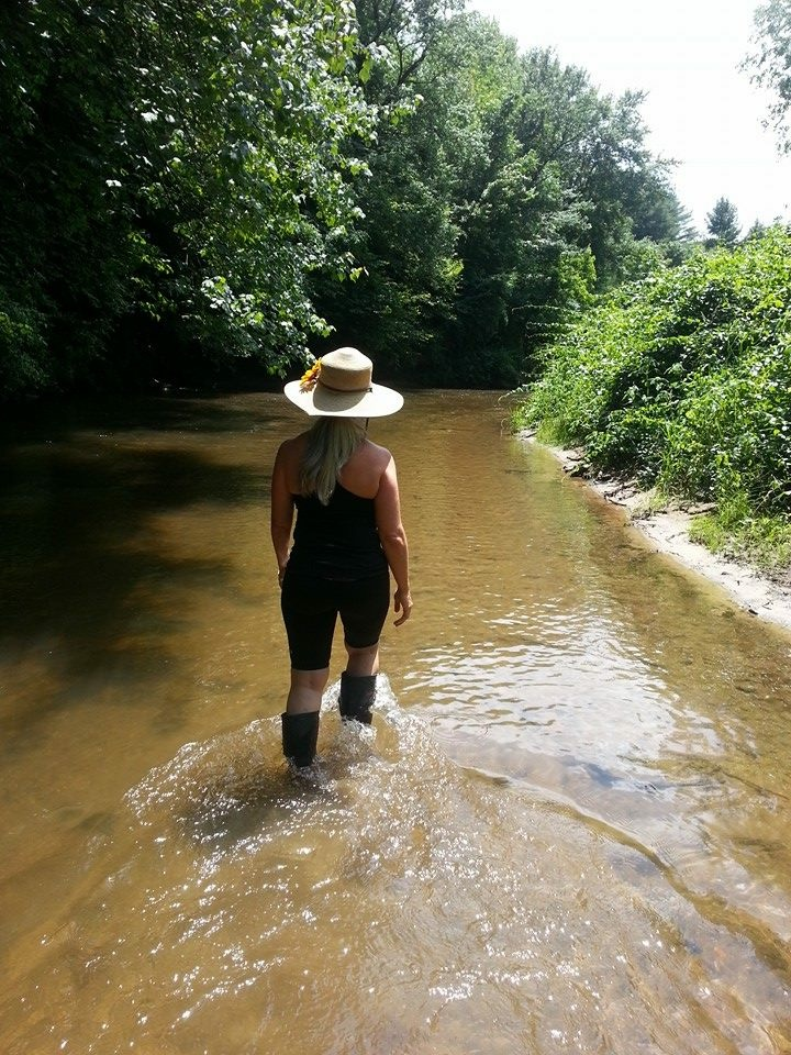 "Caroline Karp Artist walking through a creek off of a river in the North Carolina mountains to find the perfect place to paint.""It is important to pack your river walking boots when you set out to study nature."""