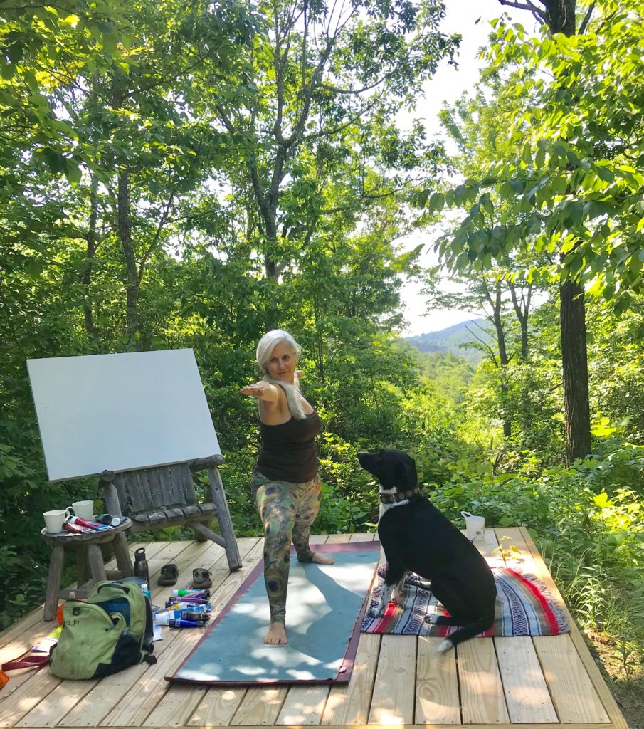 "Caroline Karp Artist and her dog Arya in a yoga pose with her canvas and paints as a backdrop as well as the North Carolina Mountains.""My ritual is to do a yoga practice before painting out in nature. Arya stays by me the entire practice"""