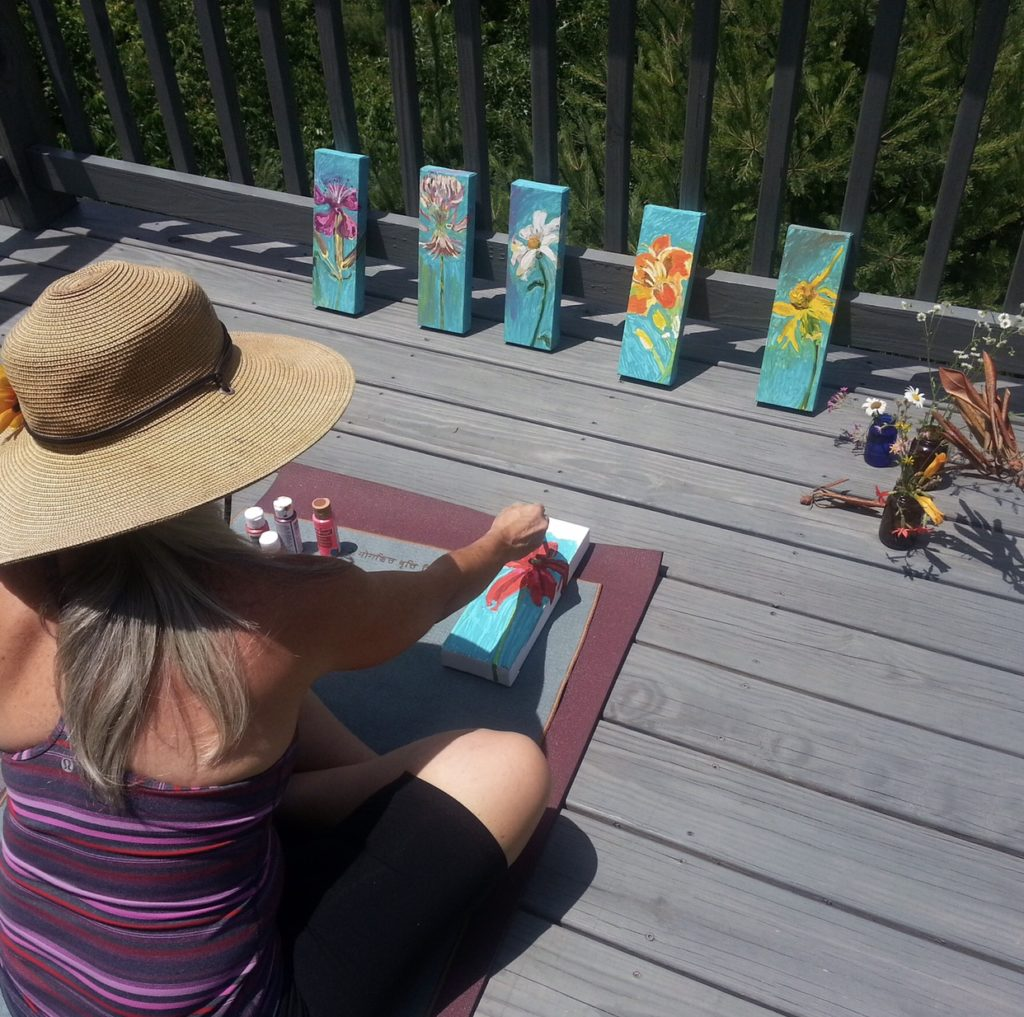 Caroline Karp Artist painting wildflowers on the sun deck of a mountain home. These flowers were picked while on a group hike after our yoga session.
