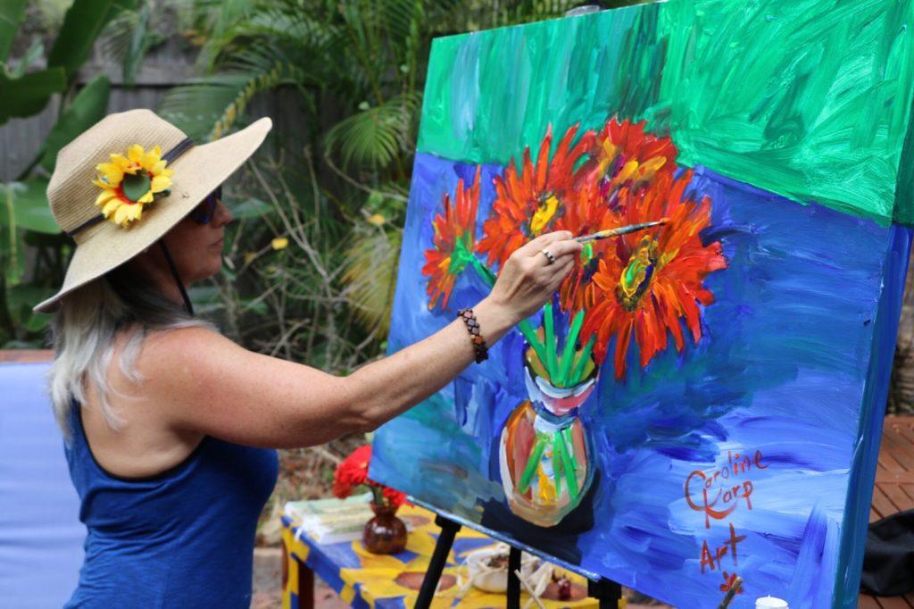 Caroline Karp Artist painting red daisies